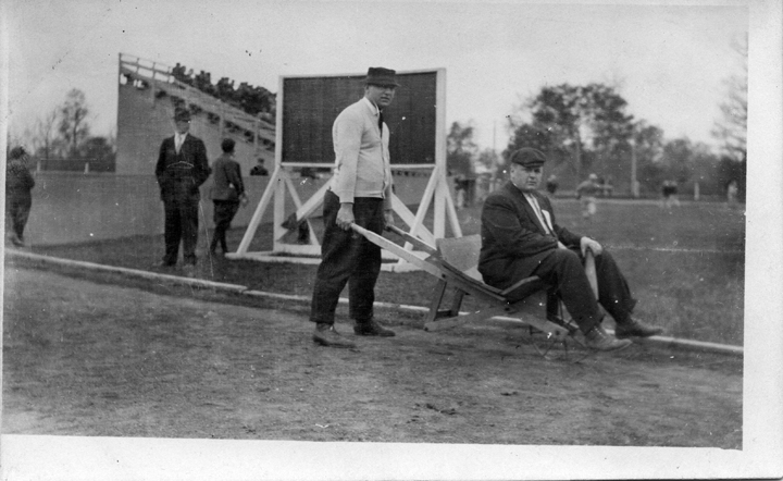 A man pushes a wheelbarrow while another man sits on it