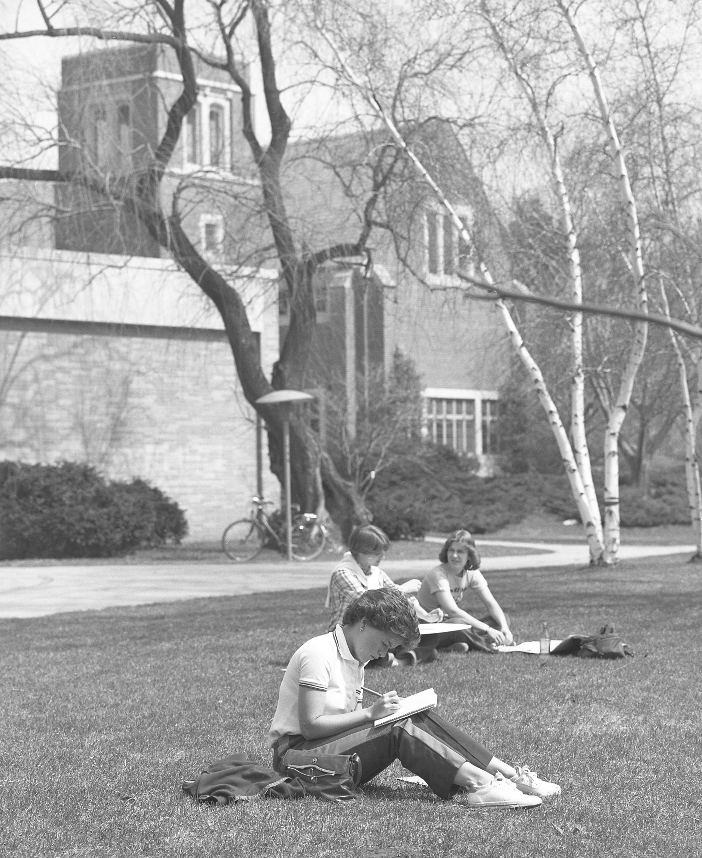 Students sitting in the grass and the Chapel; April 11, 1978