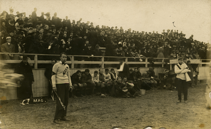 Fans, players, and cheerleaders on the sidelines at a M.A.C. football game