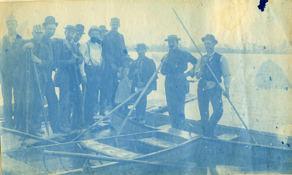 57. People standing on boats, circa 1888.