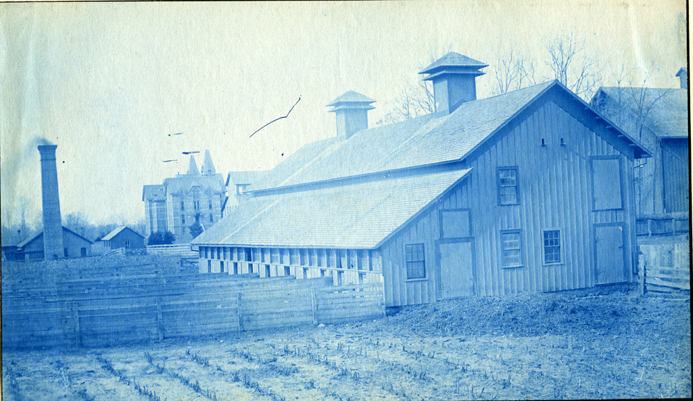 73. A barn and field with the Boiler House and Wells Hall (1), circa 1888.