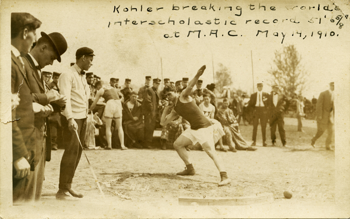 Kohler breaking the world's interscholastic shot put record at M.A.C., 1910