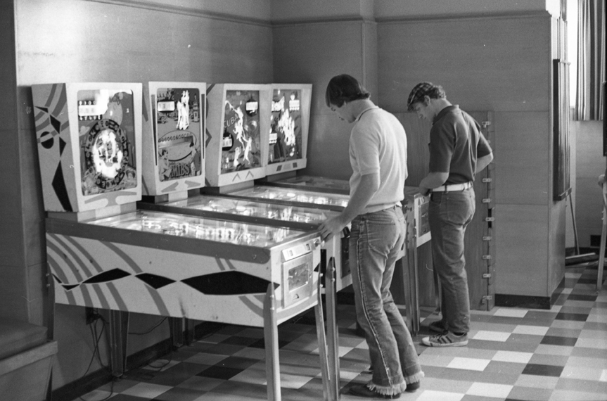Men playing pinball at the Union, 1971