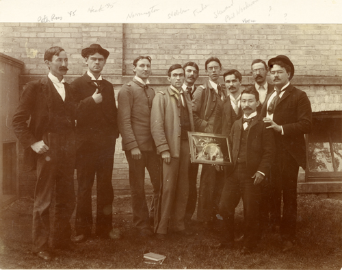 A group of students poses with a frame, 1895