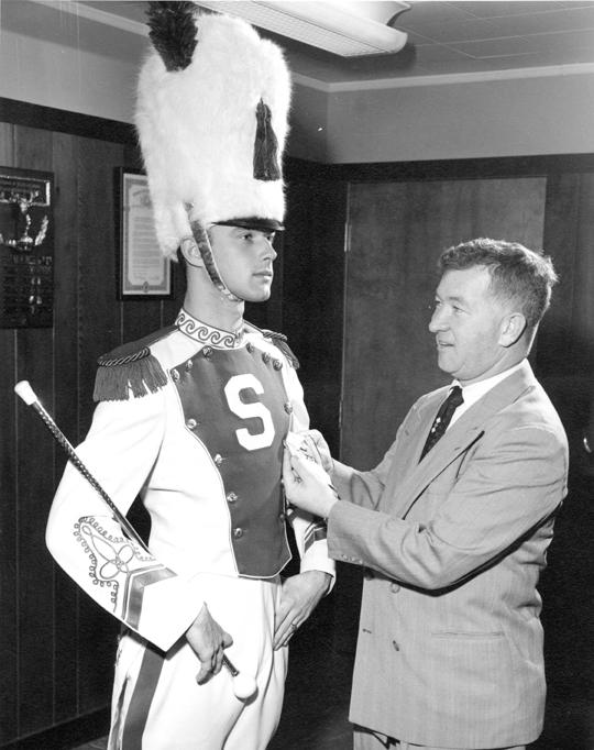 Coach Daugherty fixes a drum major's uniform, 1955
