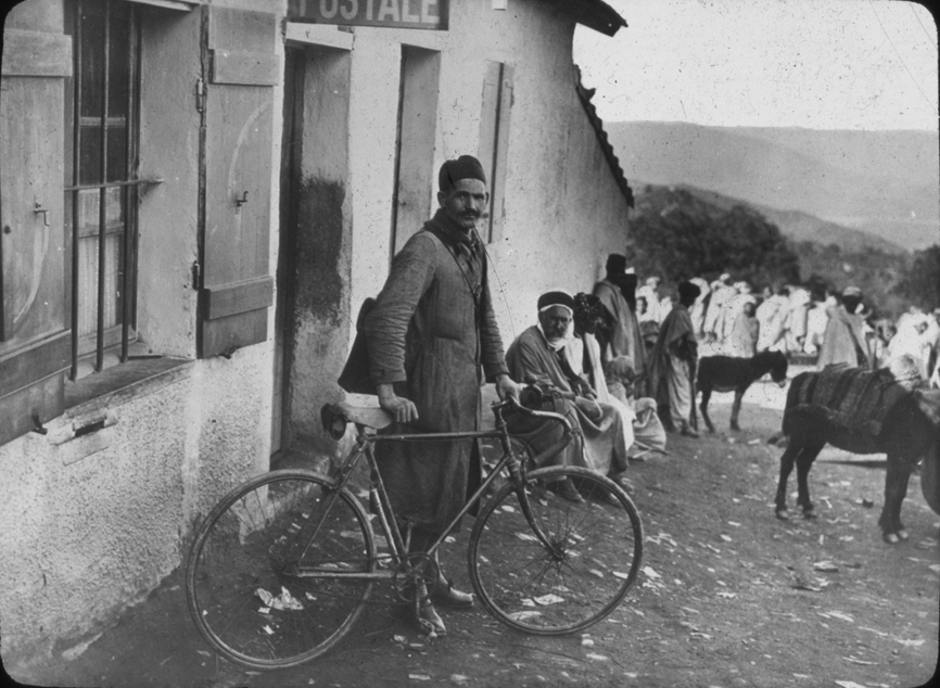 Algerian (?) man outside building with bike, undated