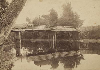 Farmer crossing bridge, date unknown