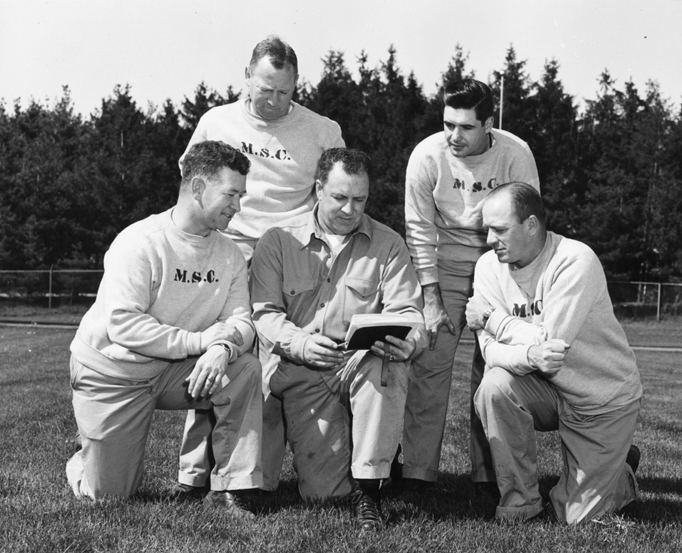MSC football coaches read from a play book, ca. 1954