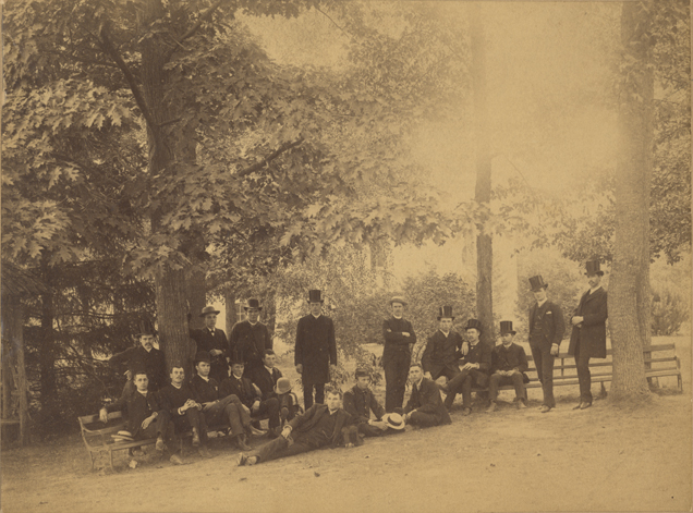 Male students pose outdoors near trees, date unknown