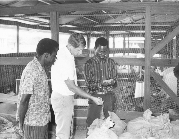 Men in the Nigeria Project examine a chicken coop, date unknown