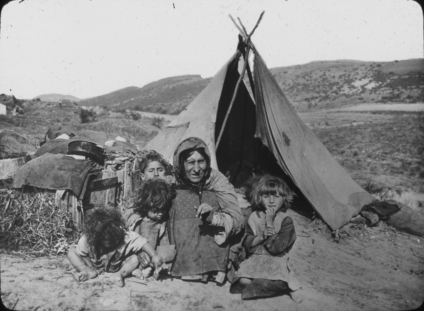 Adult and children outside tent in Austria, undated