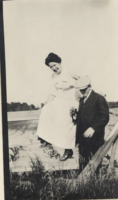 Man and woman beside fence, date unknown