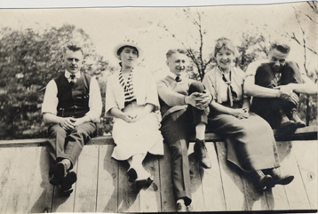 Five students sitting on a wall, date unknown