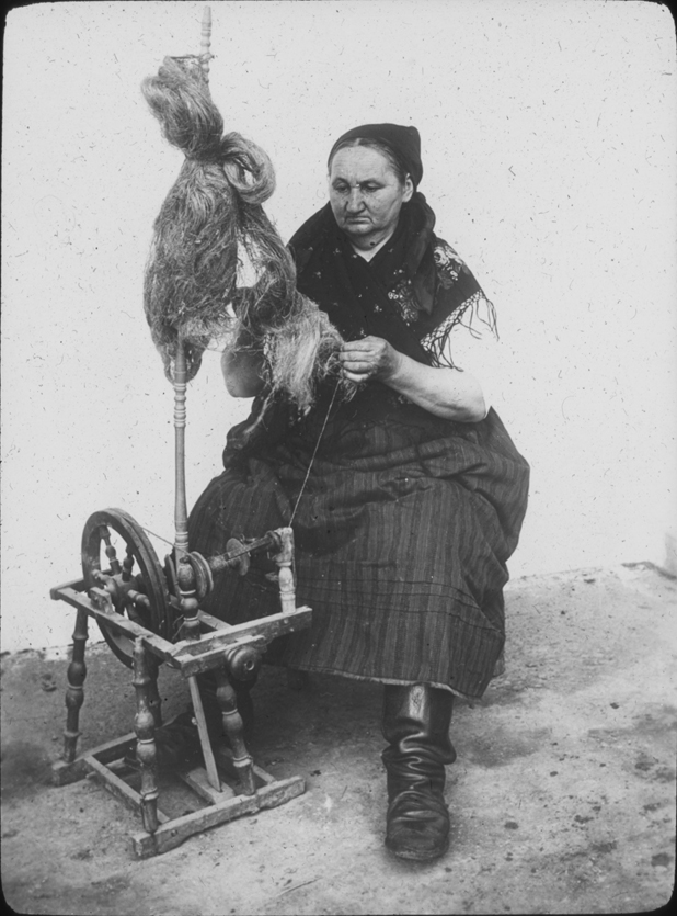 A woman in Austria spins at a wheel, undated
