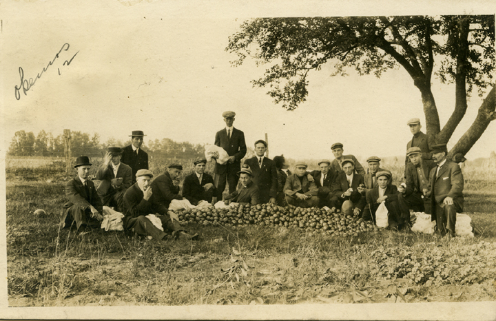 Students sit next to a pile of apples, 1912