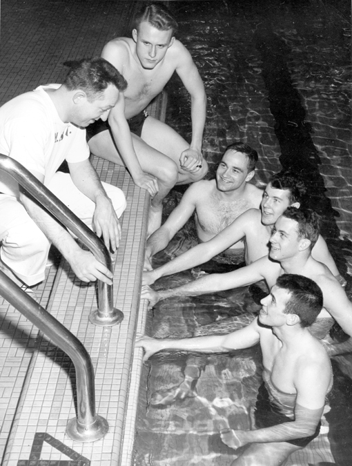 Coach Charles McCaffree speaks with swimmers, 1949