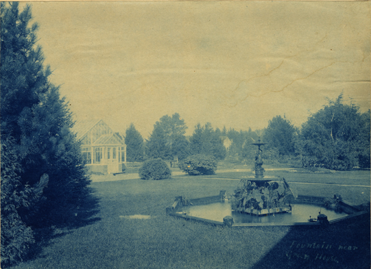 Campus fountain near a greenhouse, date unknown