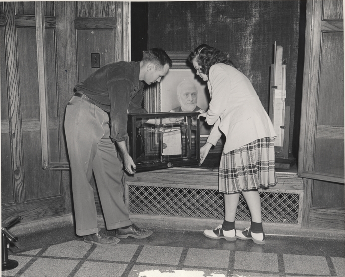 Two students move old chemistry equipment, 1947