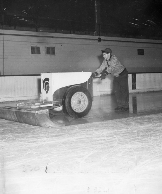 A man floods the hockey arena ice, date unknown