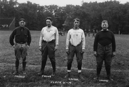 Four football coaches pose on the field, date unknown