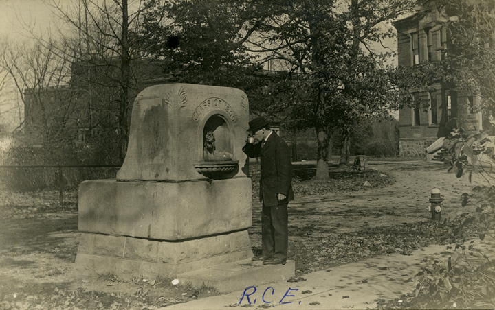 Man drinking from the Class of 1900 fountain, date unknown