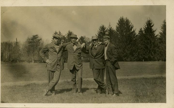 Four men standing in a field, date unknown