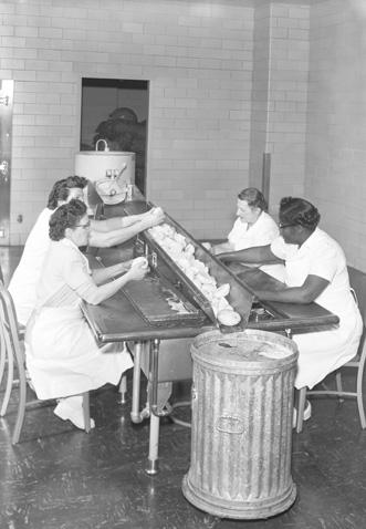 Kitchen staff preparing food, 1955