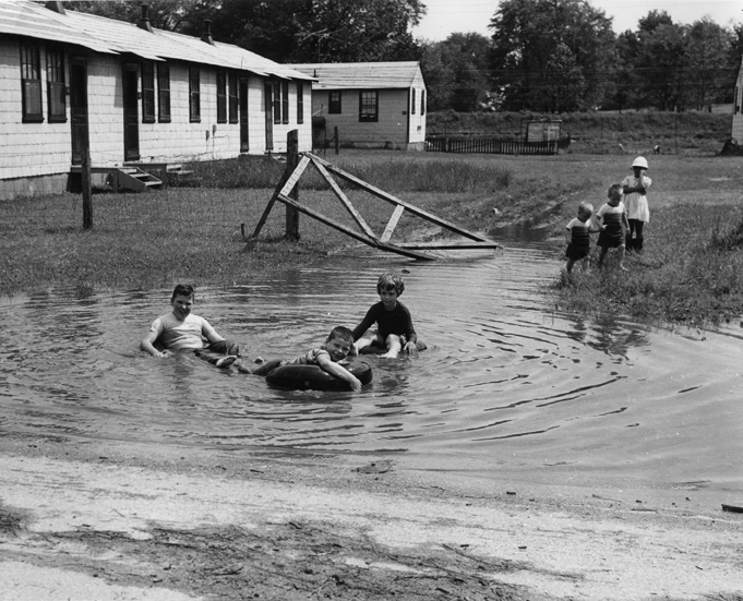 Children playing in puddle, 1956