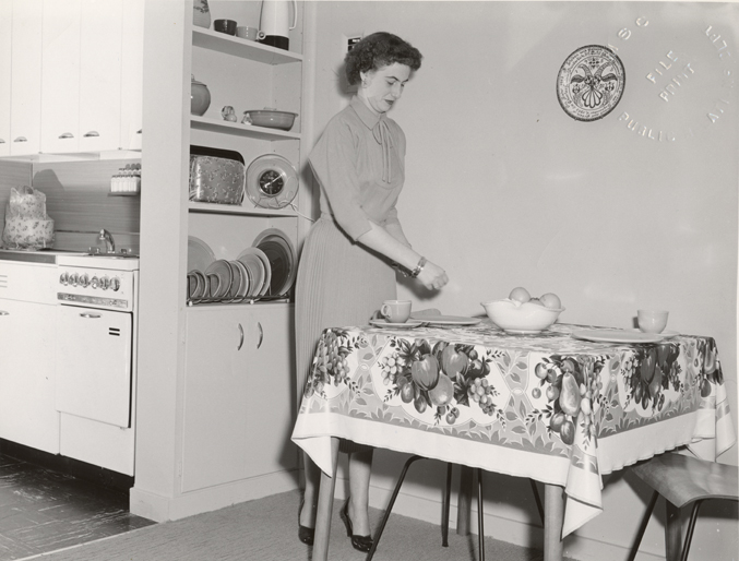 A woman sets the table in University Apartment, 1954