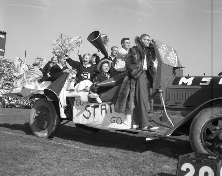 Cheerleading team in parade car, 1954