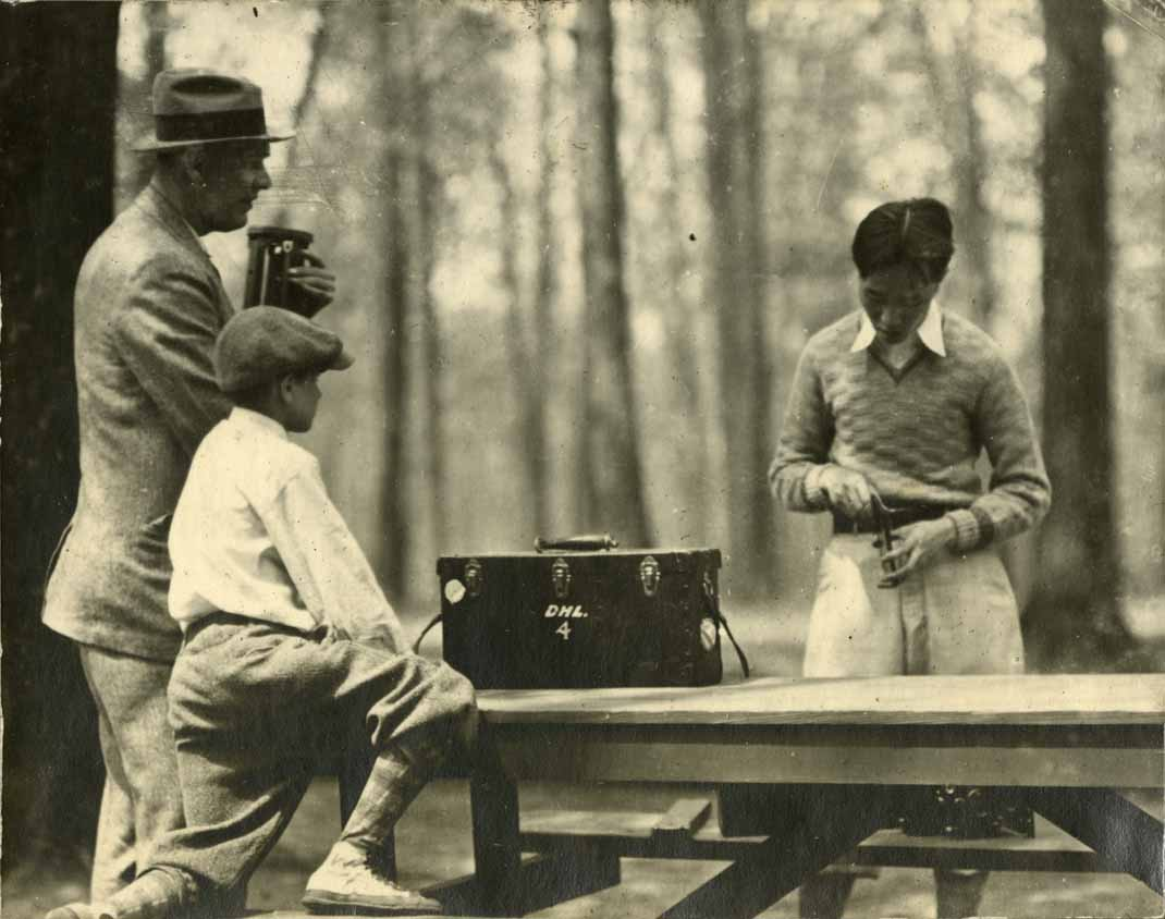 Onn Mann Liang preparing surveying equipment, circa 1924
