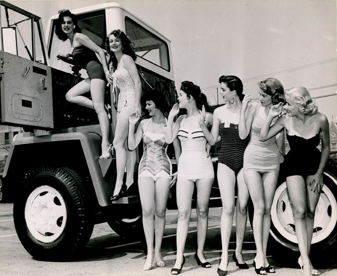 Women posing with a truck in a REO Motors advertisement, undated