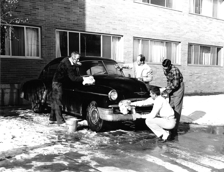 Students wash a car outside of Butterfield Hall in 1958