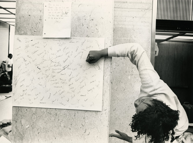 A female student signs a card during the 1989 Hannah Building student occupation.