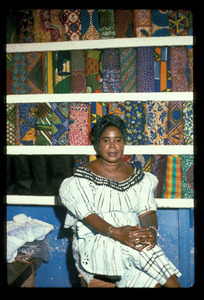 Young woman in white sitting in cloth stall