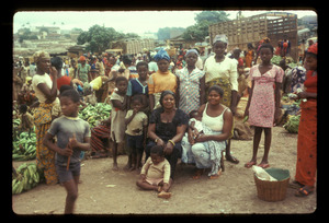 Seated woman surrounded in market by daughters and children