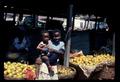 Girl, 10-12 years old, holding infant before orange stalls