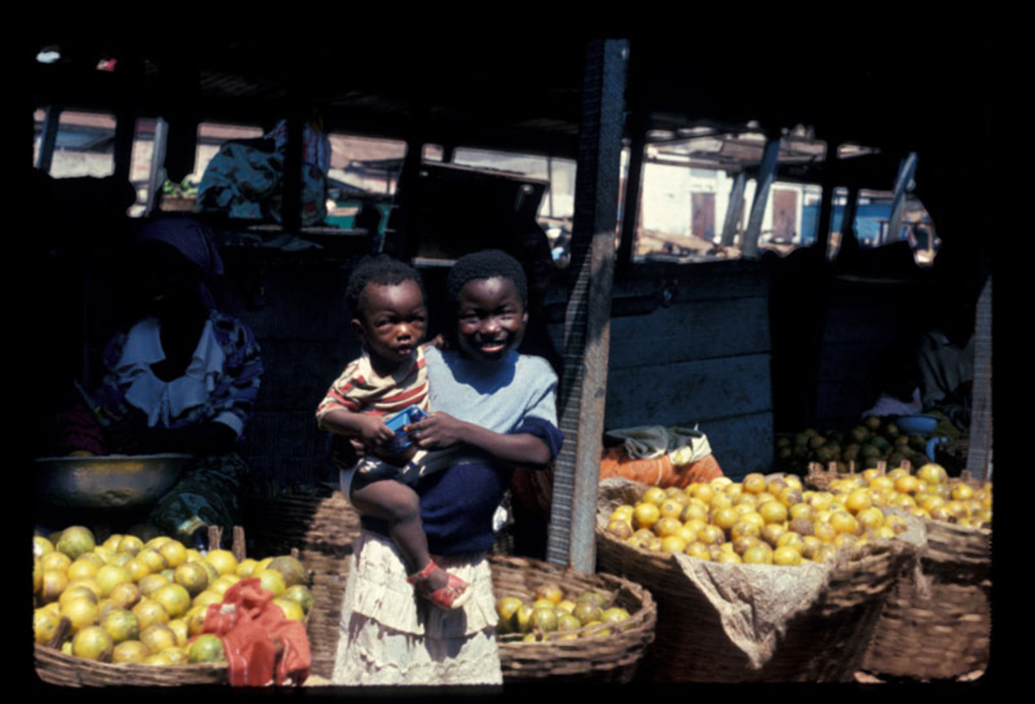 Girl, 10-12 years old, holding infant before orange stalls