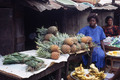 Youngish woman seated with pineapples. she sells plantain in season