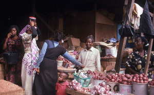 Onion trader at corner of onion shed with customers