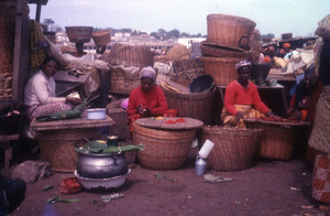 Three seated women with baskets and trays of dried pepper